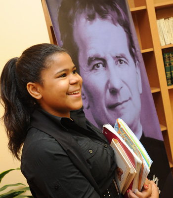 Student holding books smiling at camera